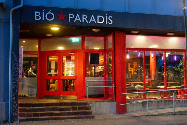 Photograph of the Bio Paradis. There are red window and door frames and fairy lights around the window.