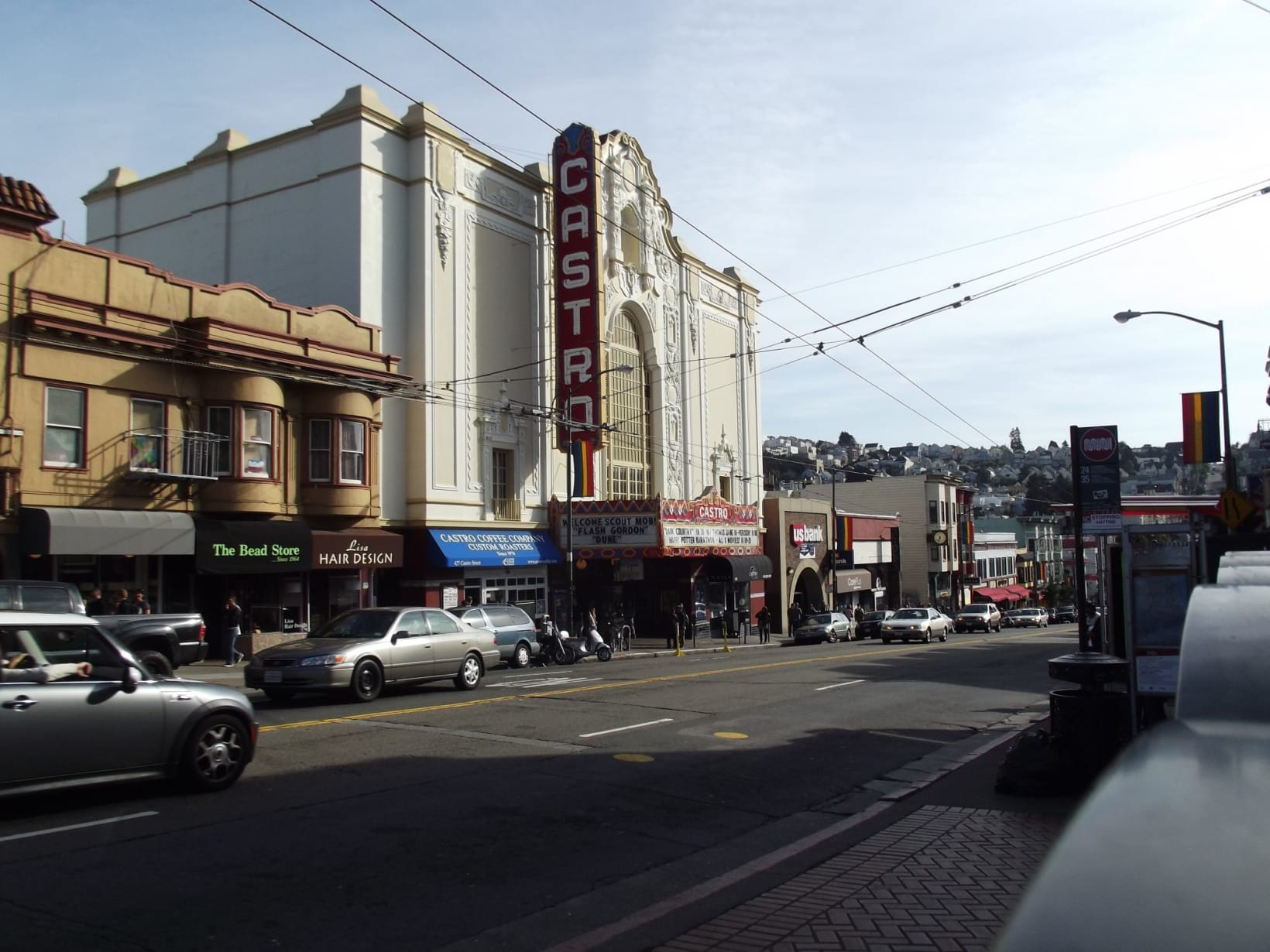 Photograph of the Castro Cinema taken from across the street. Cars are driving down the street past the cinema and other storefronts, including a bread store and a hairdressers.