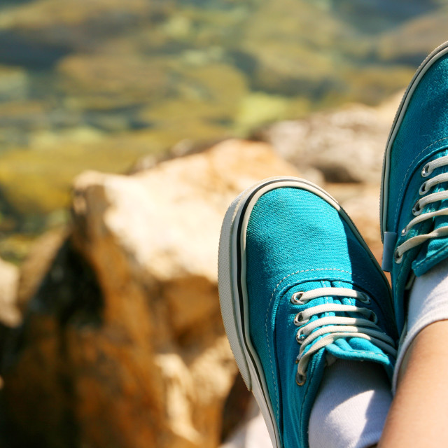 """A pair of legs in sport shoes against sea shore background"" stock image"