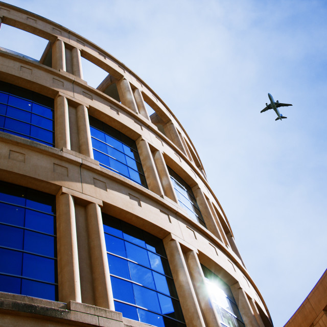"""""""Jet over Curvy Building"""" stock image"""