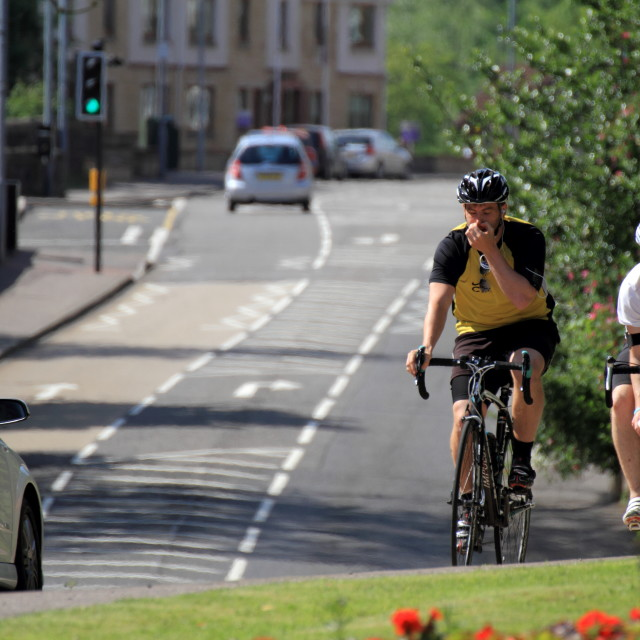 """Two male cyclists struggle in the heat, Lennoxtown, Glasgow, UK"" stock image"
