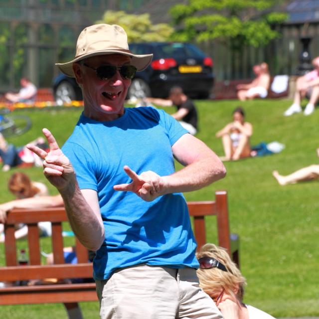 """Man dances in the sun, Botanic, Gardens, Glasgow, Scotland, UK"" stock image"