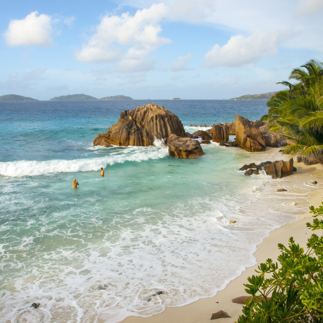 """Seychelles beach with couple swimming in the surf"" stock image"