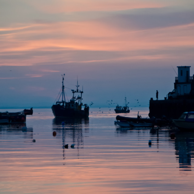 """Fishing trawler arrives home at sunset"" stock image"