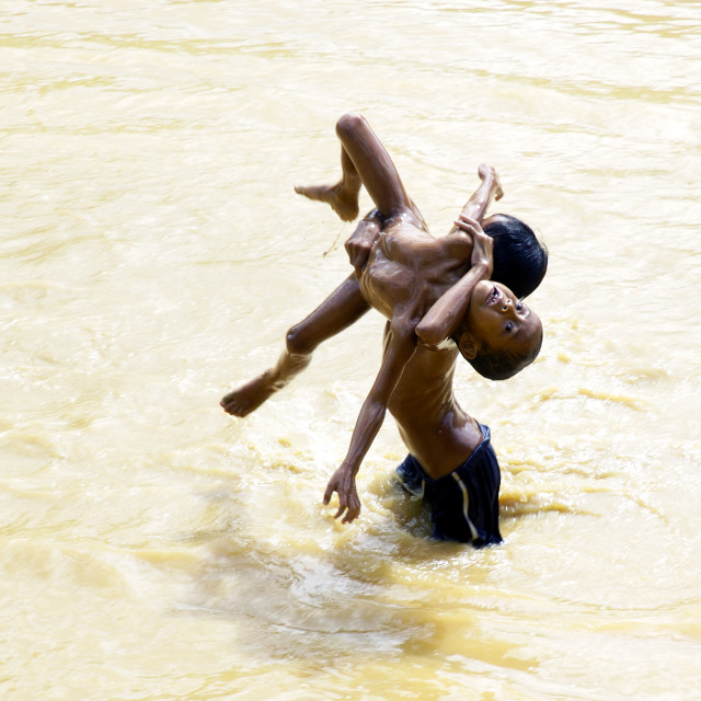 """""""Young Boys Playing In Muddy River"""" stock image"""