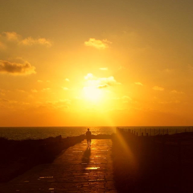 """Man walking into sunset"" stock image"