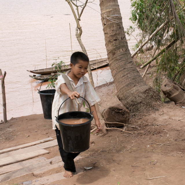 """Boy carrying buckets, Laos"" stock image"