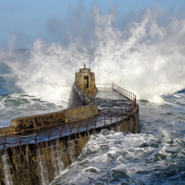 """Big wave splash on Portreath pier, Cornwall UK."" stock image"