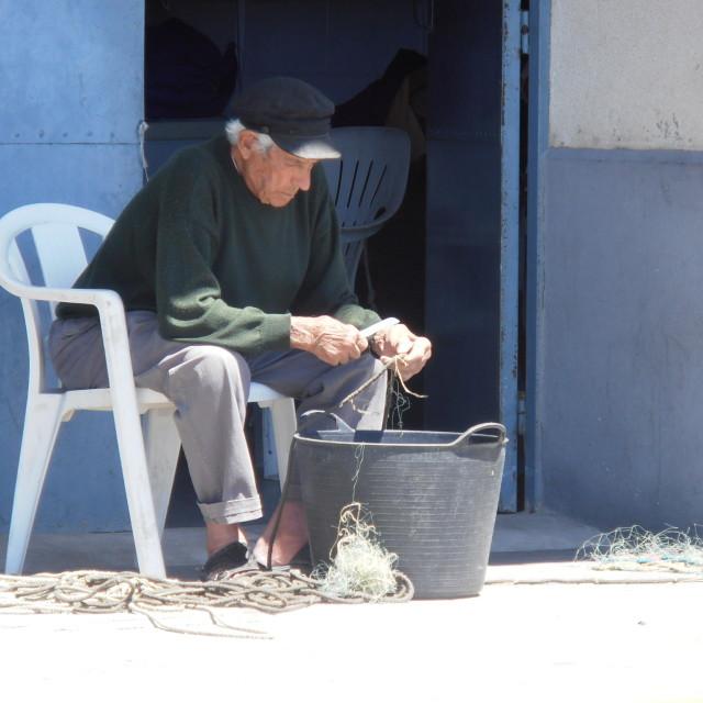 """Spanish Fisherman Mending Nets"" stock image"