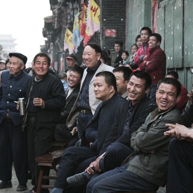 """Men watching street entertainment. Ping Yao, China"" stock image"