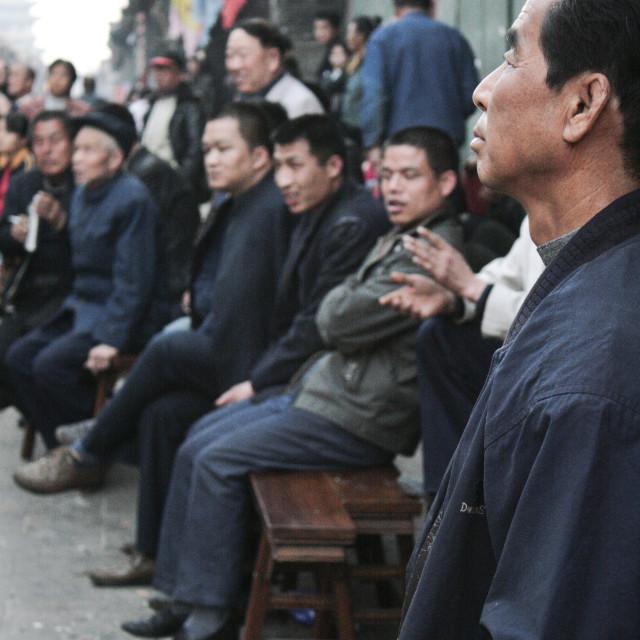 """Men watch street entertainment in Ping Yao, China."" stock image"