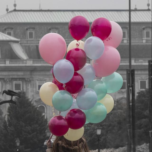 """Girl holding balloons"" stock image"