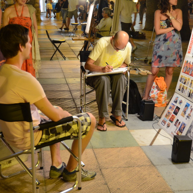 """Tourist sitting for a caricature in Nerja, Spain"" stock image"