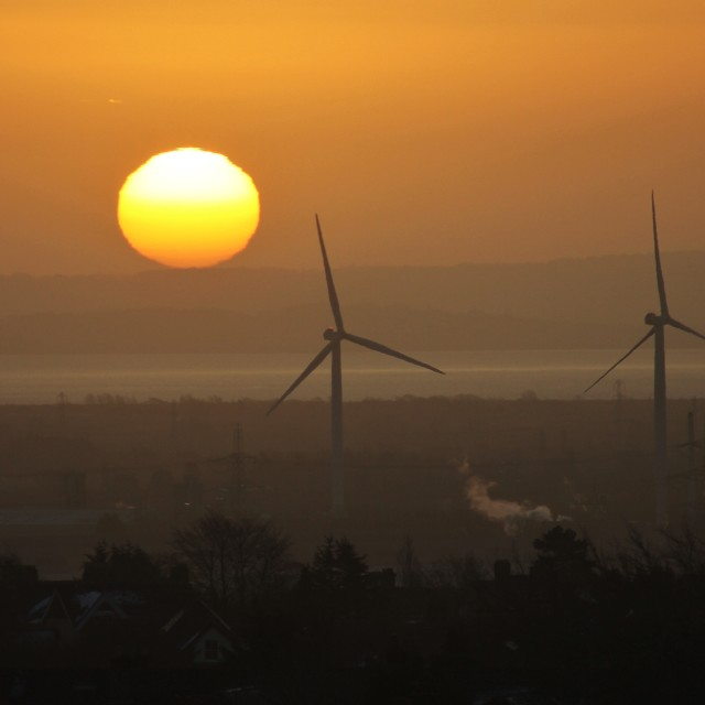 """Sunrise behind wind turbines"" stock image"