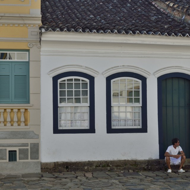 """Man sitting at a colonial house in Paraty, Brazil"" stock image"