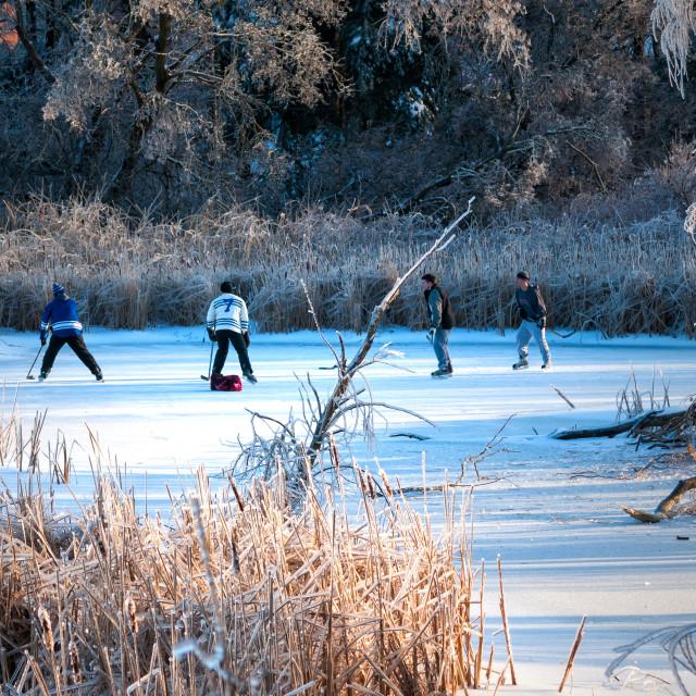 """Teens playing pond hockey"" stock image"