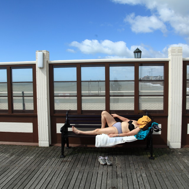 """Sunbathing on Worthing Pier"" stock image"