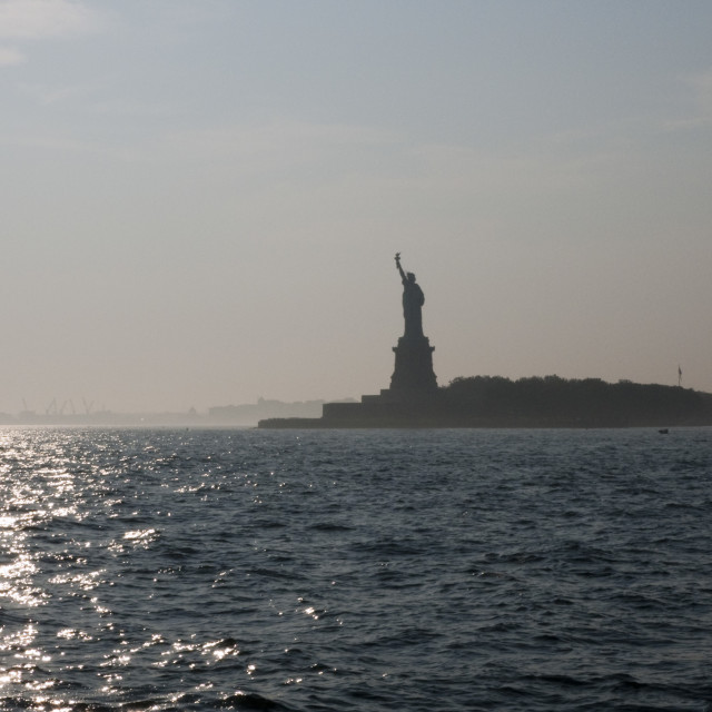 """Statue of Liberty, New York, at dusk with boat"" stock image"