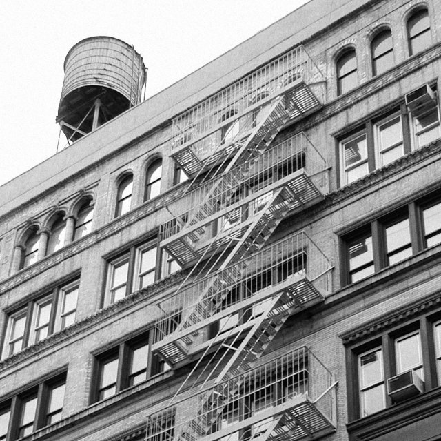 """Water tower on top of downtown building with fire escape, NY (NYC)."" stock image"
