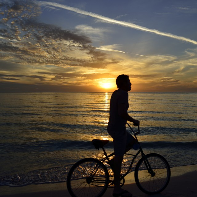 """Sunset Beach bike silhouette"" stock image"