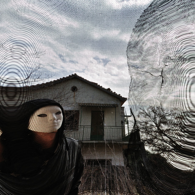"""masked evil figure behind threaded window"" stock image"