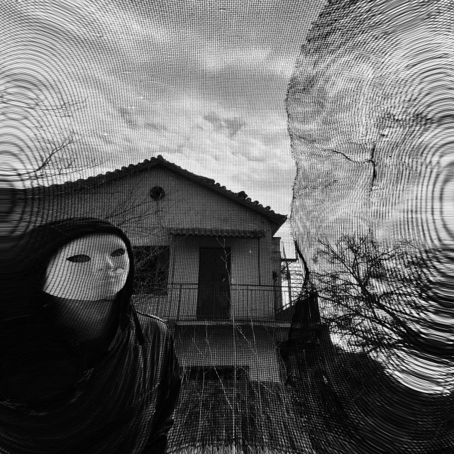 """masked figure behind threaded window"" stock image"