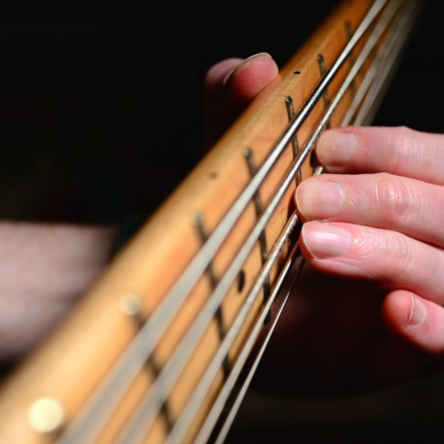 """Tattooed arm playing bass guitar"" stock image"