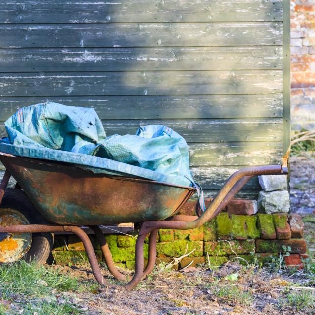 """Old rusty wheelbarrow"" stock image"