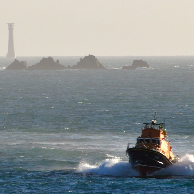 """St Marys RNLI lifeboat powers home with Bishop Rock Lighthouse in the background."" stock image"