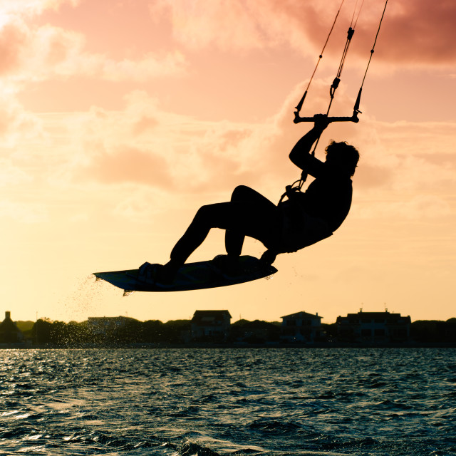 """Silhouette of a kitesurfer flying"" stock image"