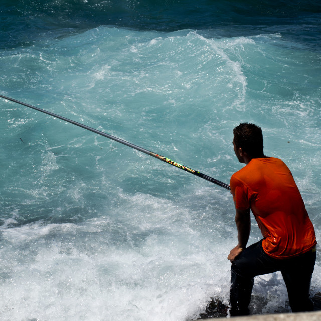 """Fishing on the rocks"" stock image"