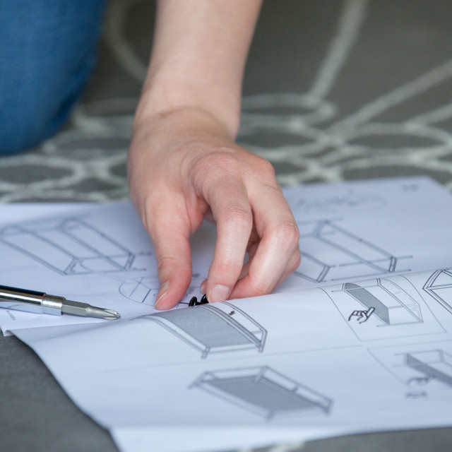 """""""Close up of hands, scerws, instructions for furniture"""" stock image"""