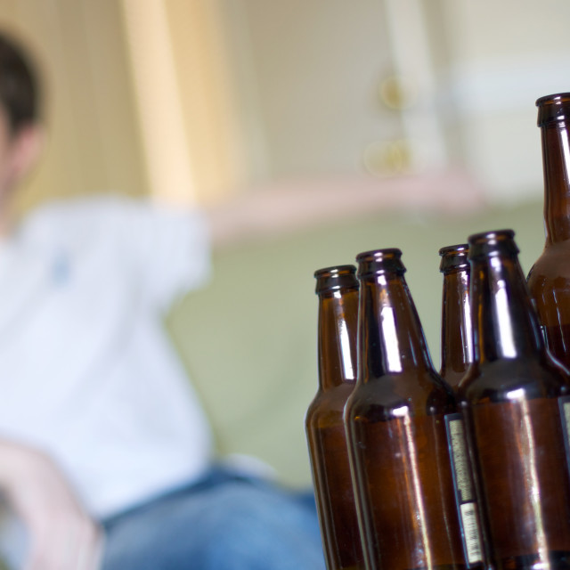 """Man facing left with group of empty beer bottles, angled"" stock image"