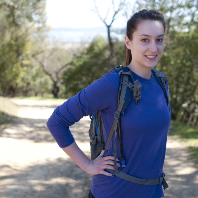 """Centered hiker woman in blue long sleeve shirt looks at camera"" stock image"