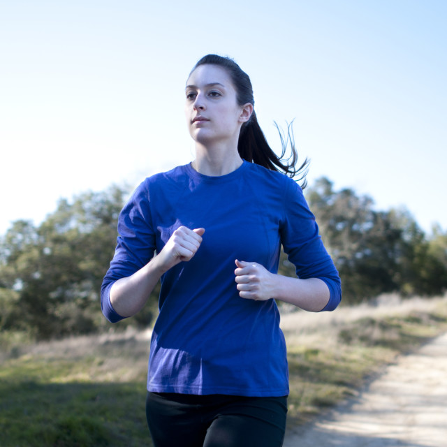 """Centered close up of woman jogging outside, facing left"" stock image"