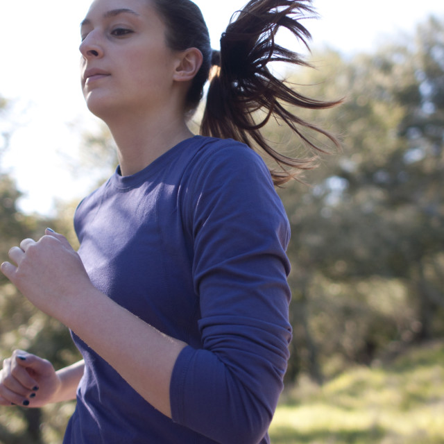 """Very close up of woman jogging, facing left"" stock image"