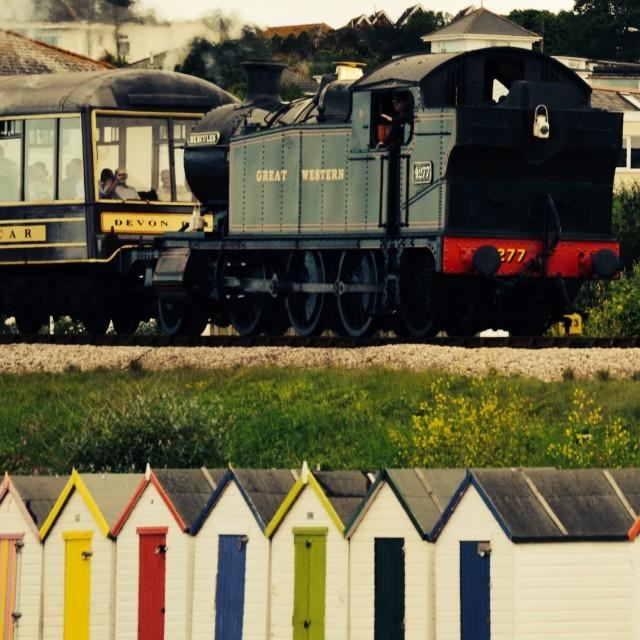 """Steam train passing beach huts"" stock image"