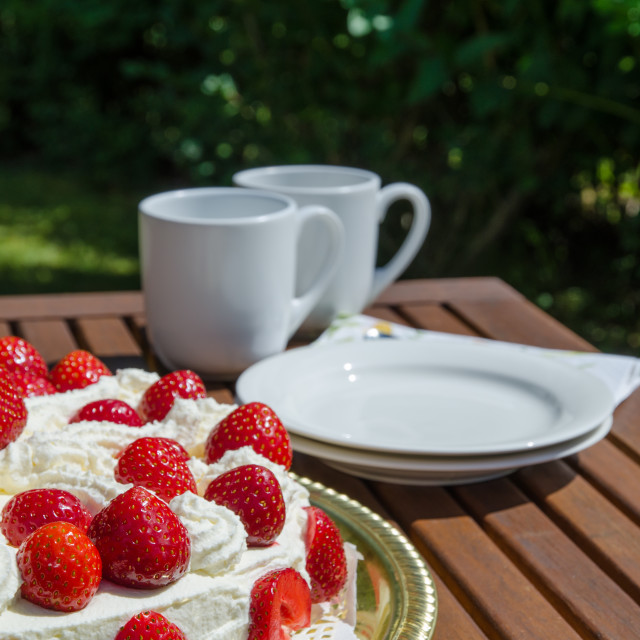 """Table with strawberry cake and coffee cups in background"" stock image"