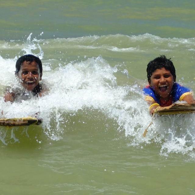 """Boys boogie boarding, India"" stock image"
