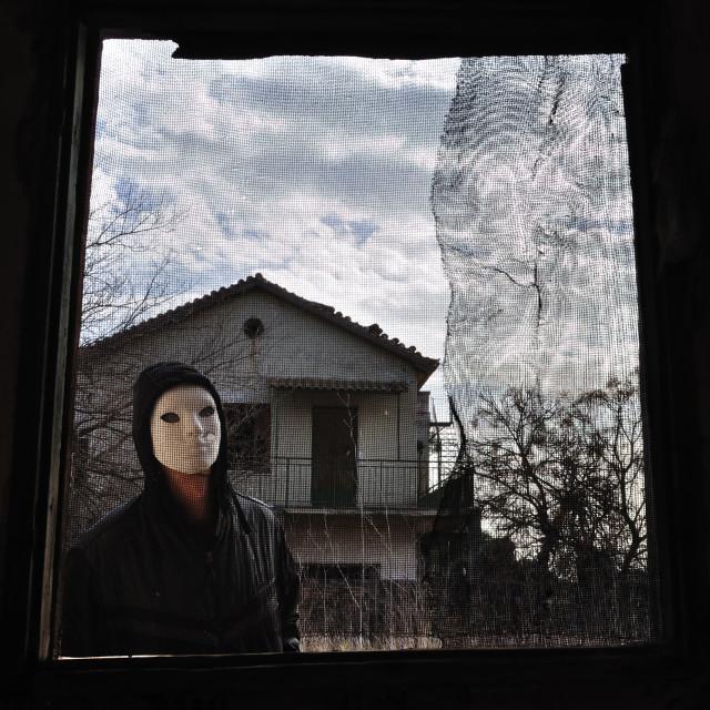 """hooded figure threaded window"" stock image"