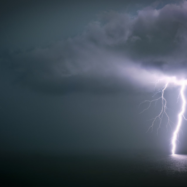 """Bolt of lightning stricking through a cloud into the ocean"" stock image"
