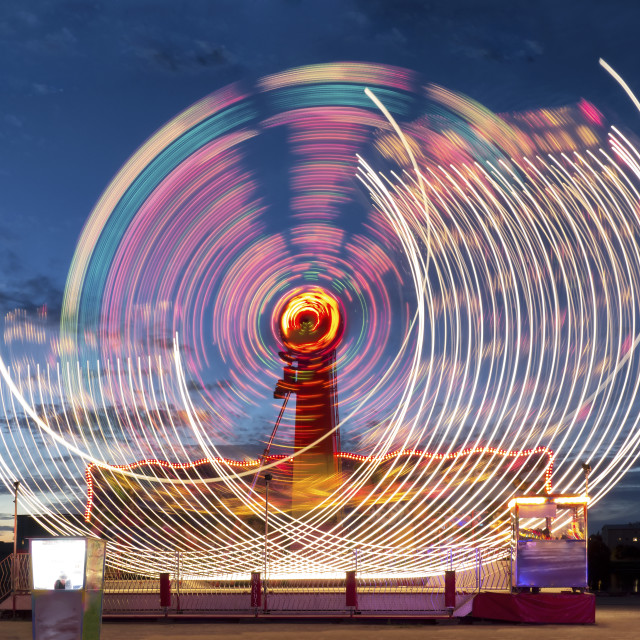 """Lighted ferris wheel in amusement park at night. Illuminated Tivoli attraction in the move."" stock image"