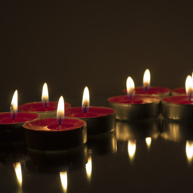 """Eight Reflected Tea Candles"" stock image"
