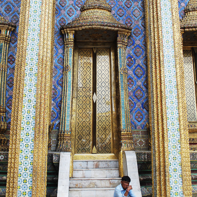 """Man on the steps of the Wat Phra Kaew"" stock image"