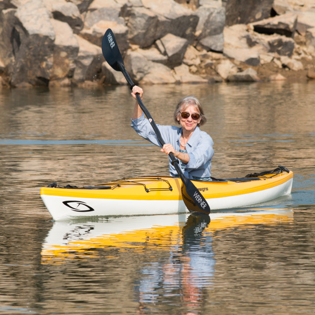 """""""Lady kayaker paddles in rocky cove. Model release."""" stock image"""