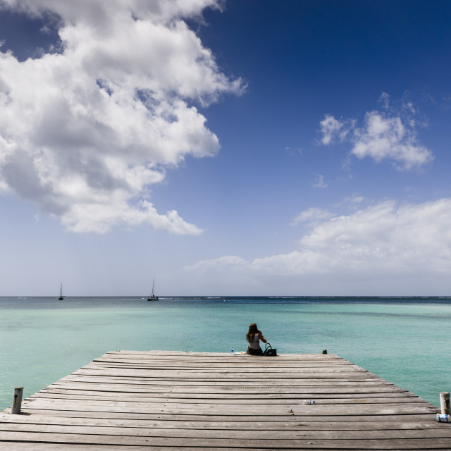 """""""Woman sitting on a pier at Pigeon Point, Store Bay, Tobago."""" stock image"""