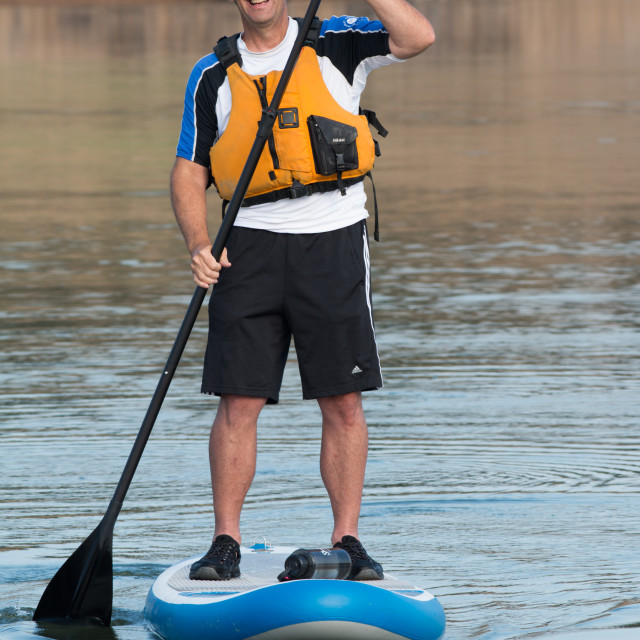 """Paddle boarder paddles near rocky cove. Model release."" stock image"
