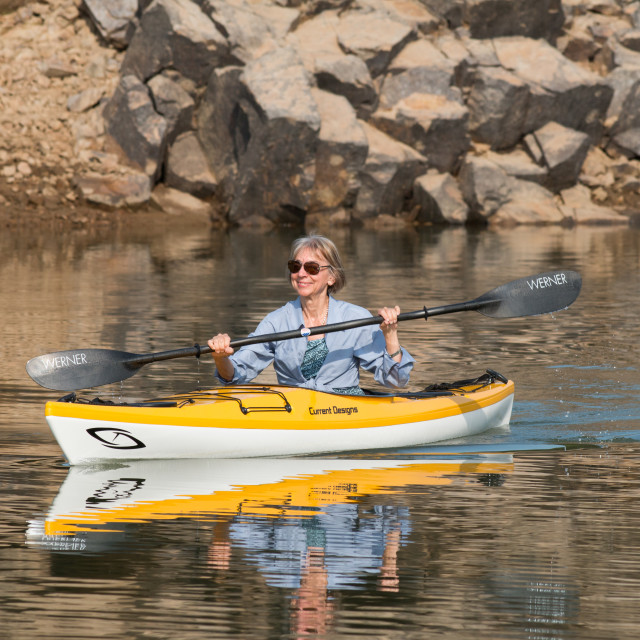 """Lady kayaker paddles in rocky cove. Model release."" stock image"