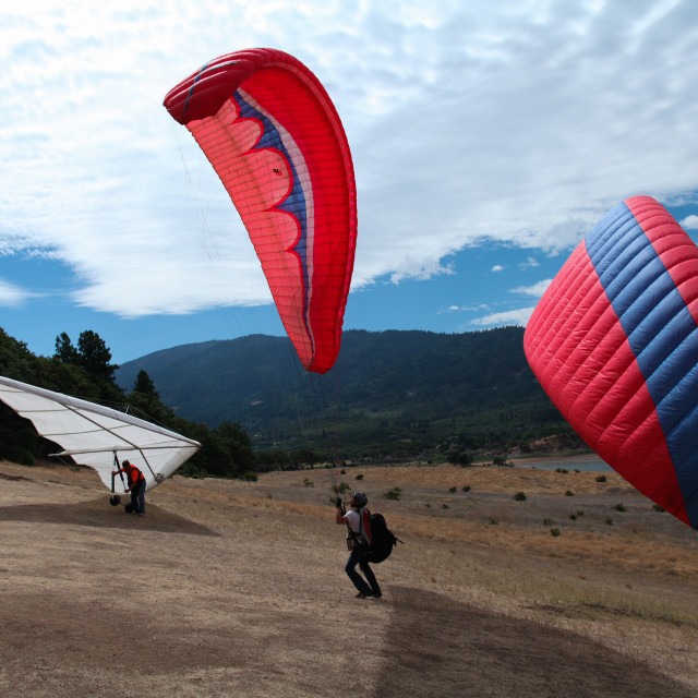 """Paragliders and hanglider make their way to the top of the hill."" stock image"