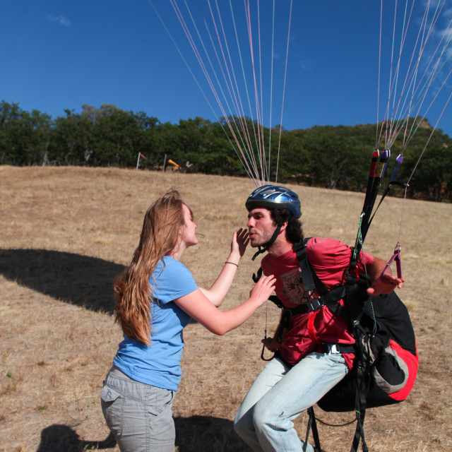 """Paraglider swoops in for a kiss."" stock image"